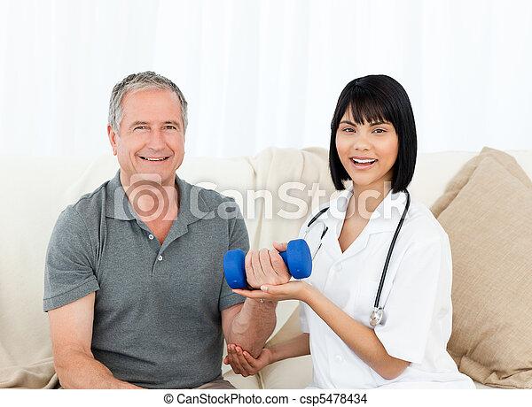 La enfermera ayuda a su paciente a hacer ejercicios - csp5478434