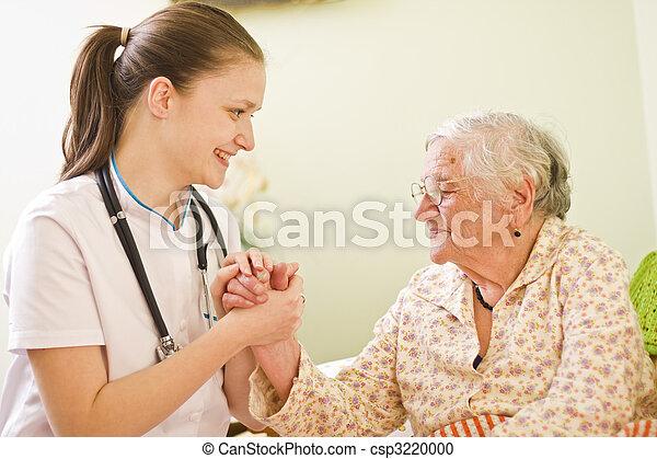 Una joven doctora visitando a una anciana enferma socializando - hablando - con ella, sosteniendo sus manos. - csp3220000