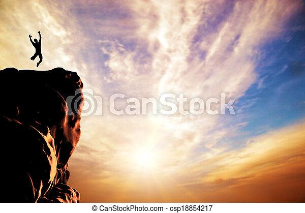 Una silueta de un hombre saltando de alegría en la cima de la montaña, acantilado al atardecer - csp18854217